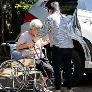 carer helping elderly woman from wheel chair into car