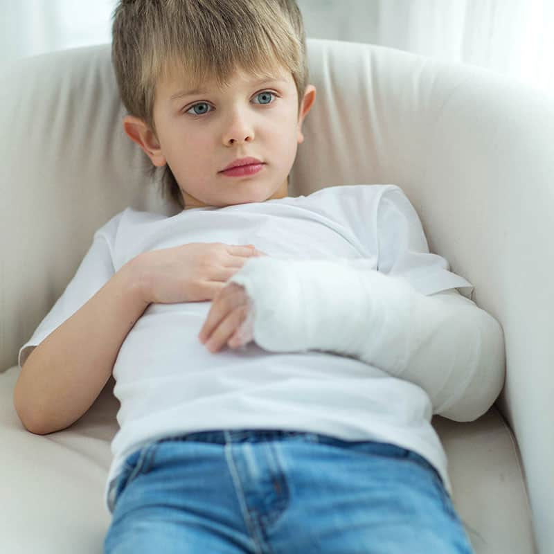 young boy with broken arm in plaster
