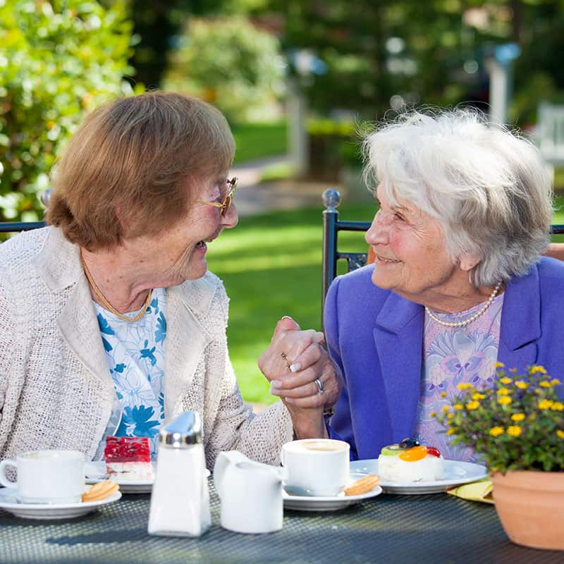 elderly women sharing afternoon tea and laughing together