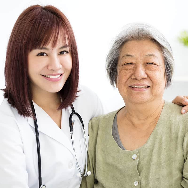 smiling women doctor with stethoscope with elderly asian woman