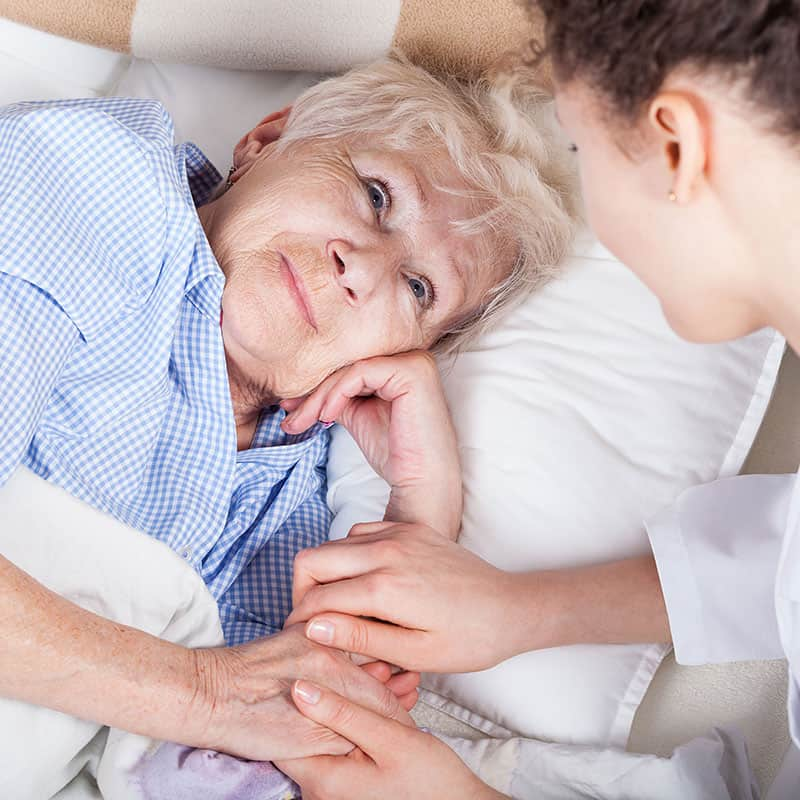 carer holding hand of palliative care women