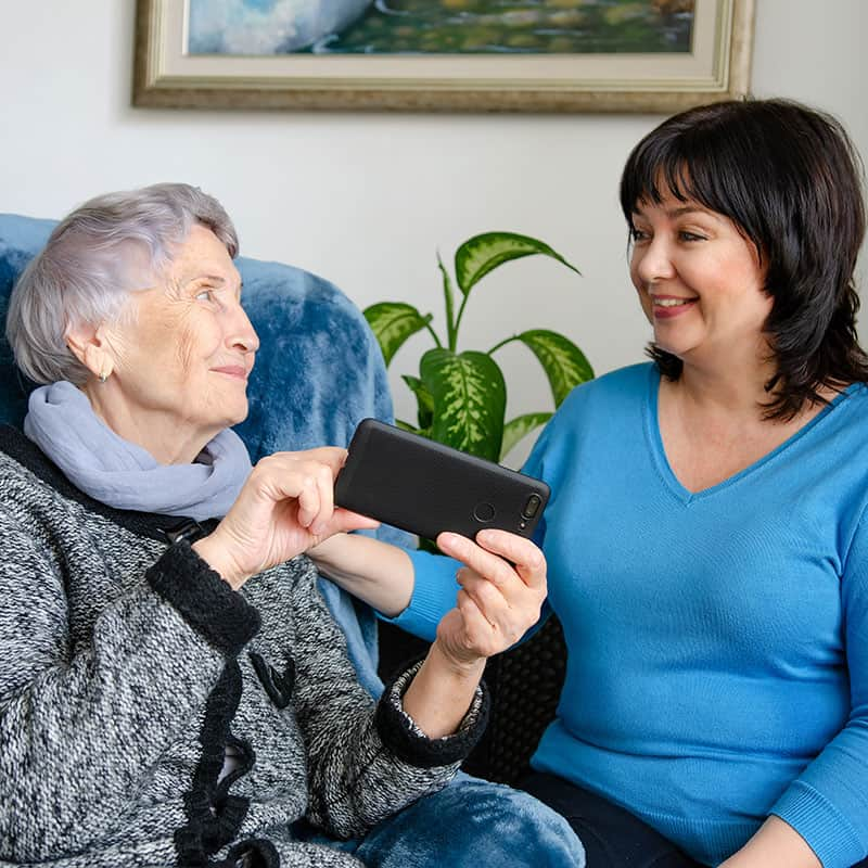 elderly woman showing carer phone screen